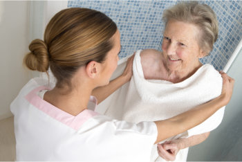 caregiver assisting the elder woman for bathing